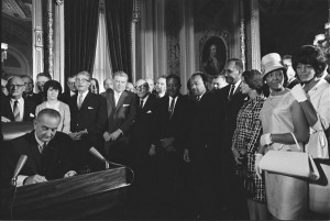 Photograph of President Lyndon Johnson signing the Voting Rights Act as Martin Luther King, Jr., and other civil rights leaders look on, Washington, DC, April 6, 1965. (National Archives Identifier 2803443).